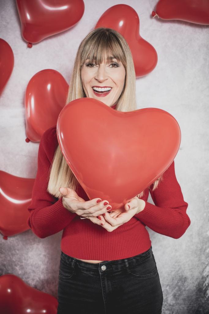 Model in rotem Pulli vor Herzwand